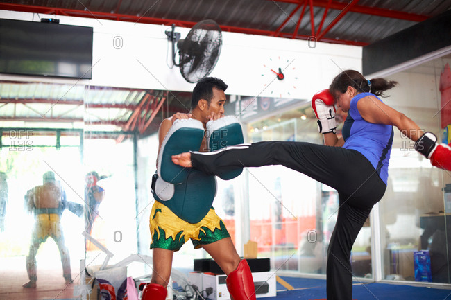 Mature woman practicing kickboxing with male trainer in gym
