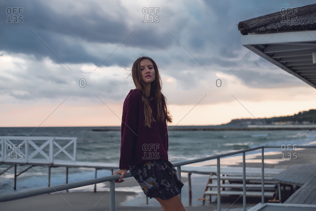 Portrait of young woman with long hair leaning against beach pier at dusk, Odessa Oblast, Ukraine