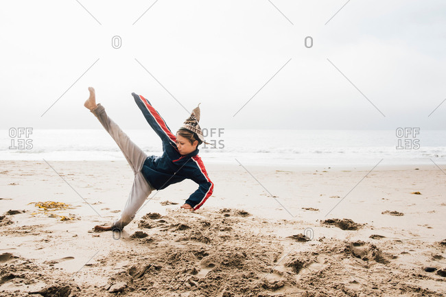 Young boy on beach, practicing martial arts, leg raised in kick