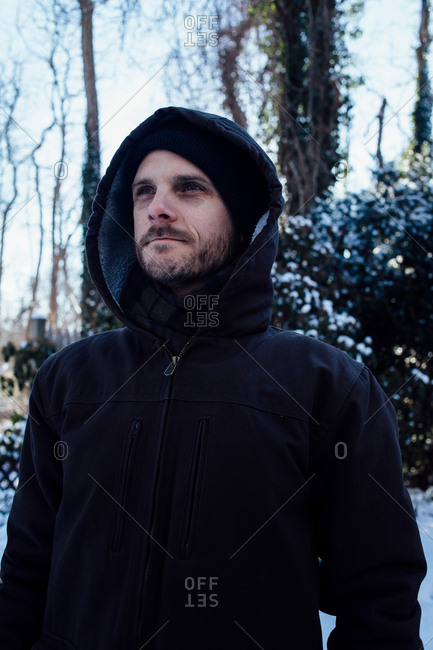Man keeping warm in hooded jacket in winter weather
