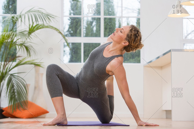 Woman at home, doing yoga, in yoga position