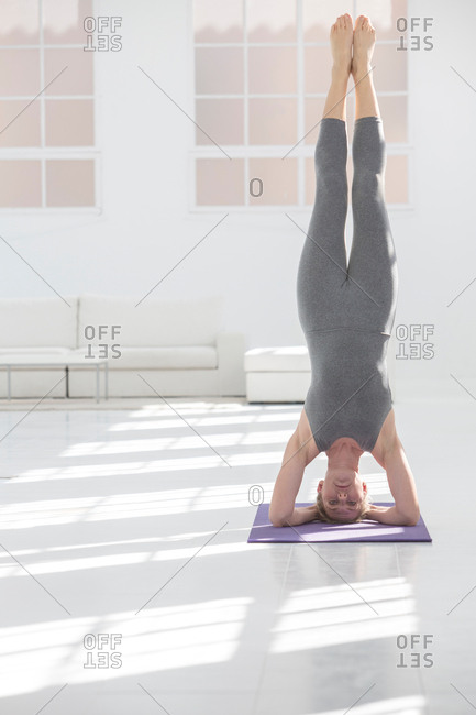Woman at home, doing yoga, doing headstand, in yoga position