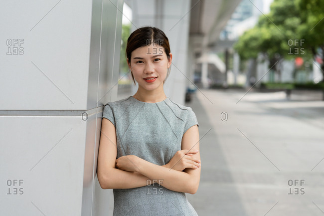 Portrait of young businesswoman leaning against wall in city, Shanghai, China