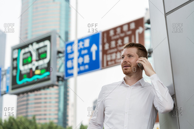 Young businessman making smartphone call in city, Shanghai, China