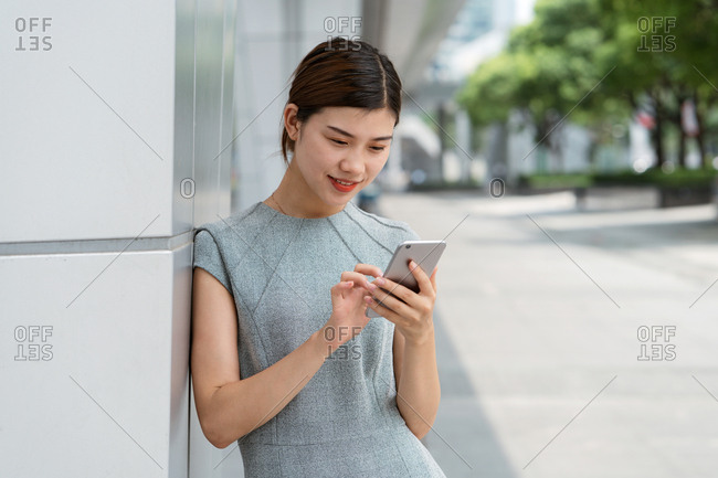 Young businesswoman using smartphone touchscreen in city, Shanghai, China