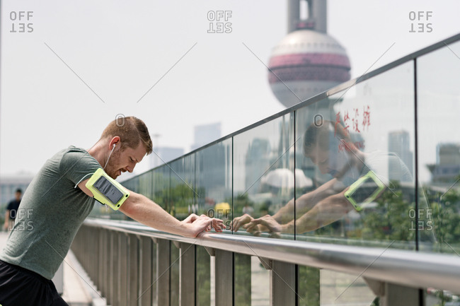 Young male runner leaning against handrail in Shanghai financial center, Shanghai, China