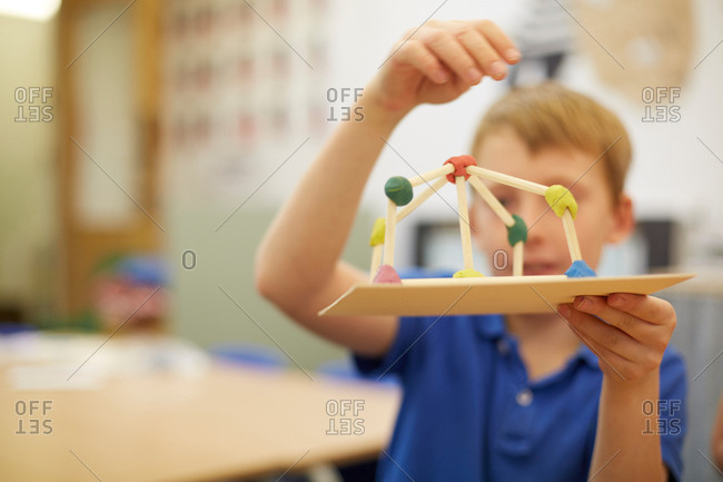 Schoolboy making ball and stick model in classroom at primary school