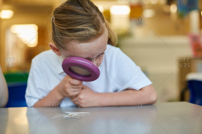 Schoolgirl looking through magnifying glass in classroom lesson at primary school