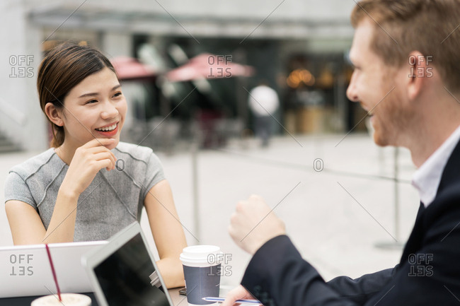 Young businesswoman and man having discussion at sidewalk cafe