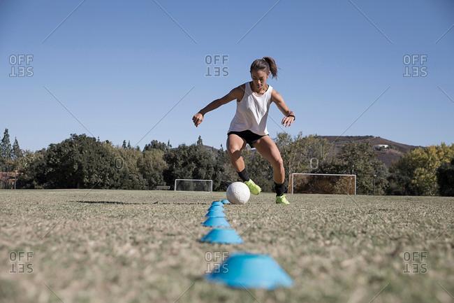 Woman dribbling football