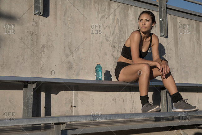 Portrait of woman in sport clothing sitting on bench looking away