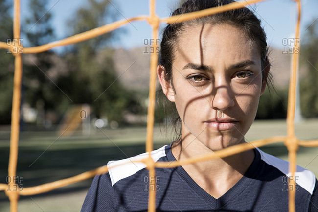 Portrait of woman behind football goal netting looking at camera