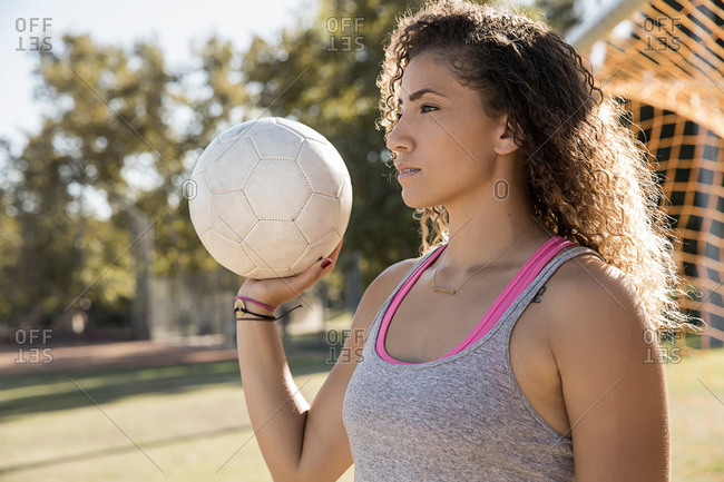 Portrait of woman holding football looking away