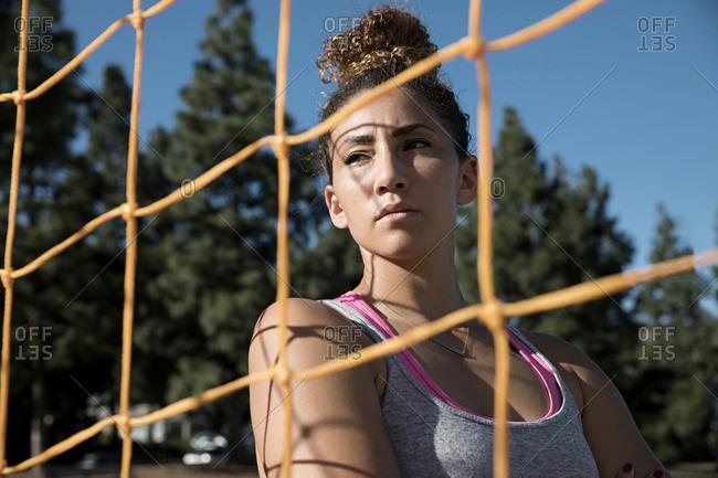 Portrait of woman behind football goal netting looking away