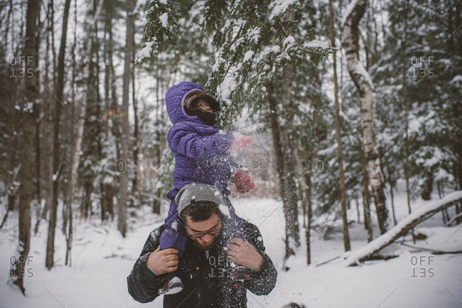 Father and daughter in snowy landscape, father carrying daughter on shoulders