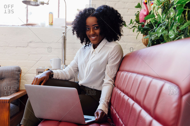 Woman in office sitting on sofa using laptop, looking at camera smiling