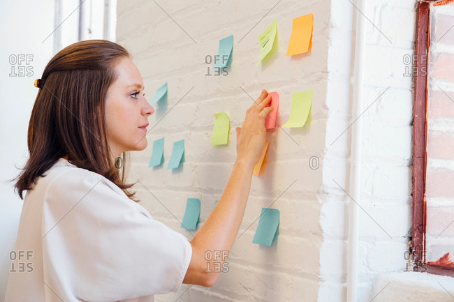 Woman sticking sticky notes to brick wall