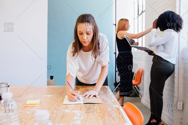 Woman in office writing in notepad