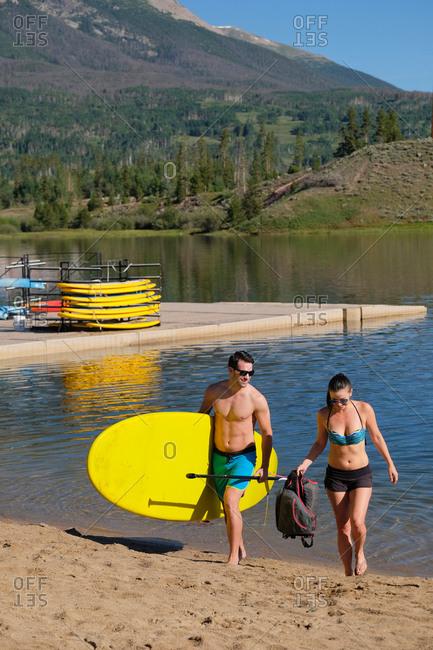 Paddleboarding couple carrying paddleboard on lake shore, Frisco, Colorado, USA