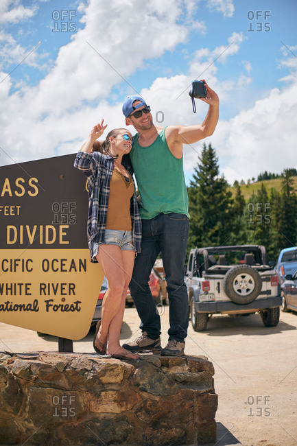 Couple taking selfie by car park Continental Divide sign, Breckenridge, Colorado, USA