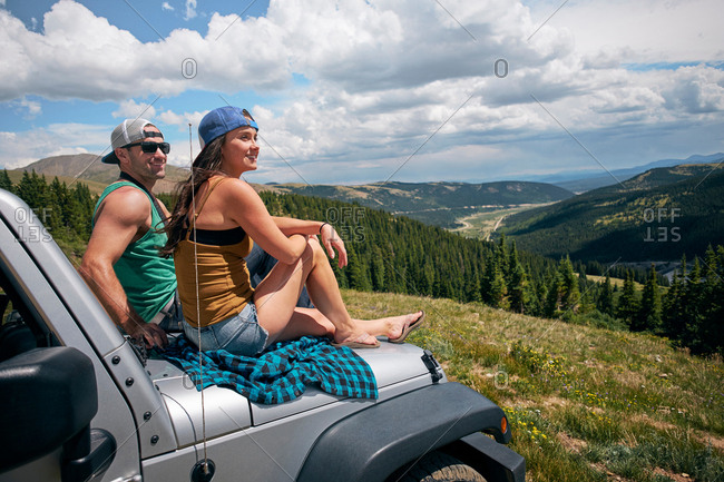 Road trip couple looking from car hood in Rocky Mountains, Breckenridge, Colorado, USA