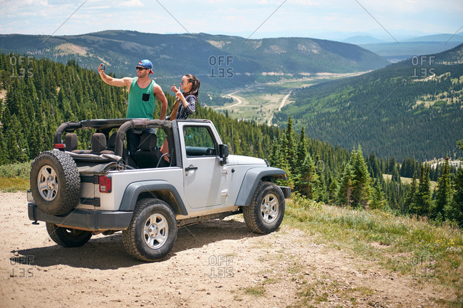 Road trip couple in parked four wheel convertible taking selfie in Rocky mountains, Breckenridge, Colorado, USA