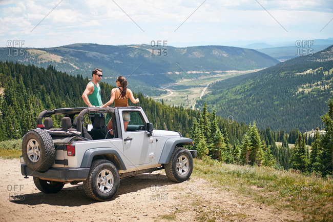 Road trip couple in parked four wheel convertible in Rocky mountains, Breckenridge, Colorado, USA