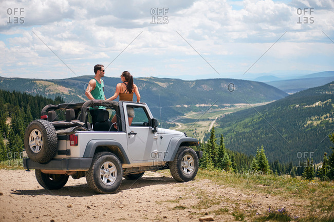 Road trip couple in four wheel convertible in Rocky mountains, Breckenridge, Colorado, USA