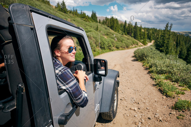 Young woman on road trip looking from car window in Rocky mountains, Breckenridge, Colorado, USA