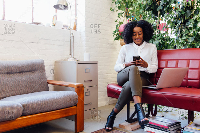 Woman in office sitting on sofa with laptop, texting on smartphone