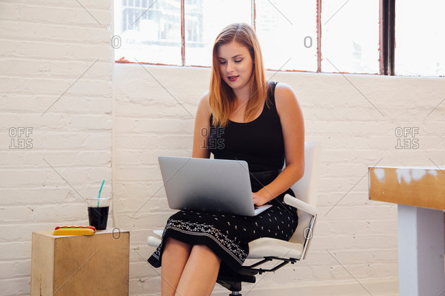 Woman in office chair using laptop