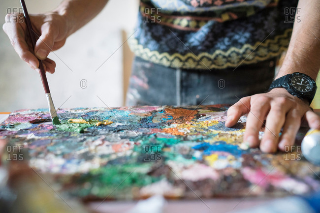 Male artist mixing oil paint on palette in artists studio, close up of hands
