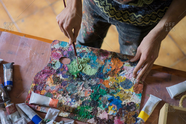 Male artist mixing oil paint on palette in artists studio, mid section