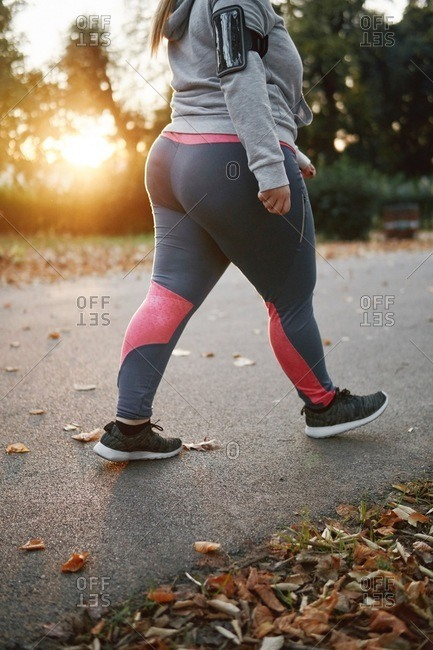 Curvaceous young woman training, neck down view walking in park