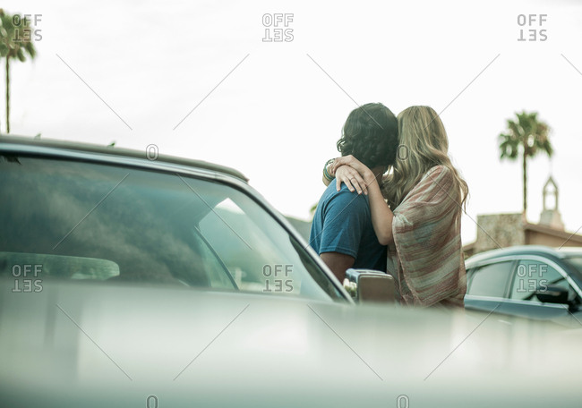 Young couple, standing beside car, hugging, looking away