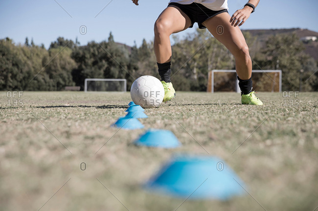 Cropped view of woman dribbling football