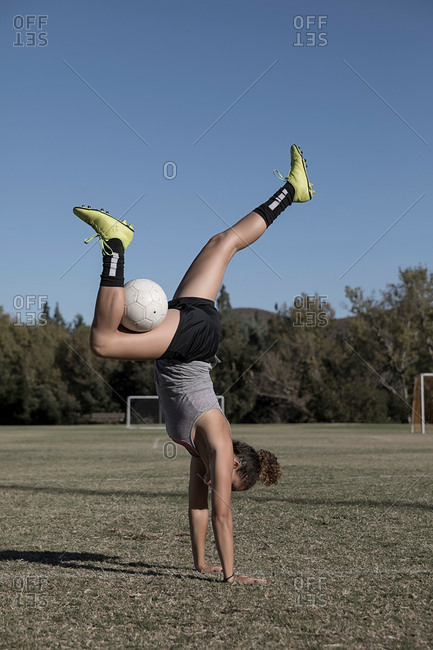 Women on football pitch doing handstand with football