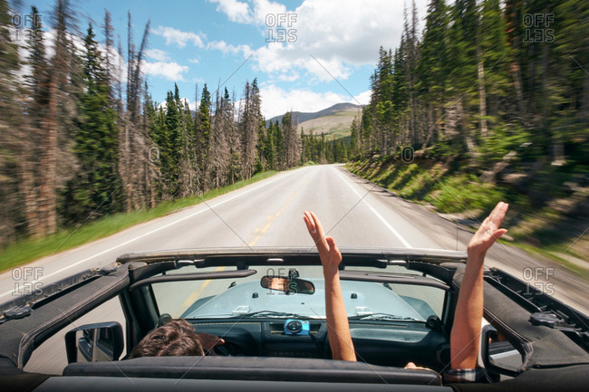 Road trip couple driving convertible on rural highway with hands raised, Breckenridge, Colorado, USA