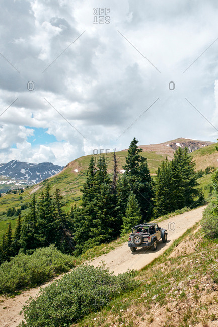 Road trip couple driving convertible off road vehicle on rural mountain road, Breckenridge, Colorado, USA