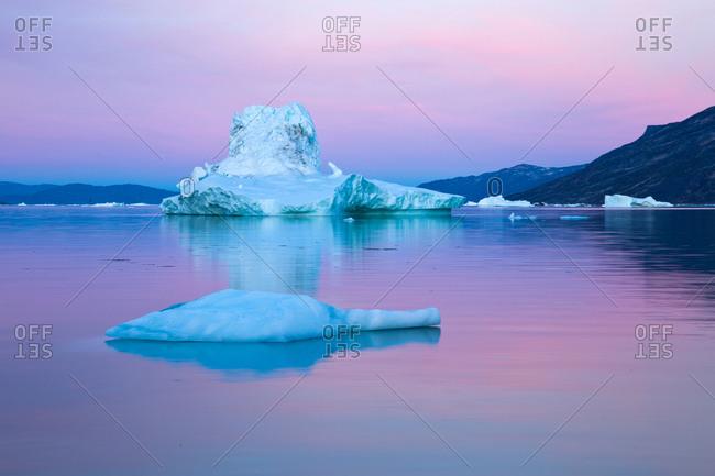 Icebergs in calm water during midnight sun, Jakobshavn, Vestgronland, Greenland