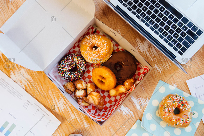 Overhead view of doughnuts in cake box on desk