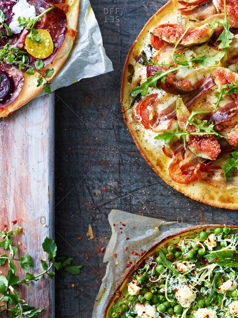 Three fresh pizzas, cropped overhead view