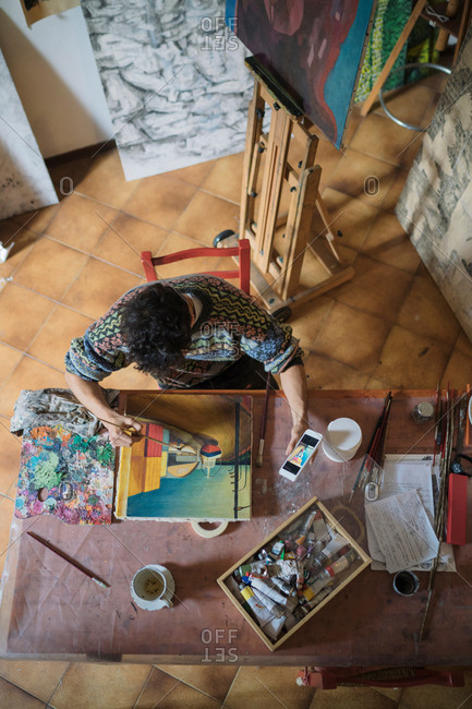 Male artist looking at smartphone while painting canvas in artists studio, overhead view