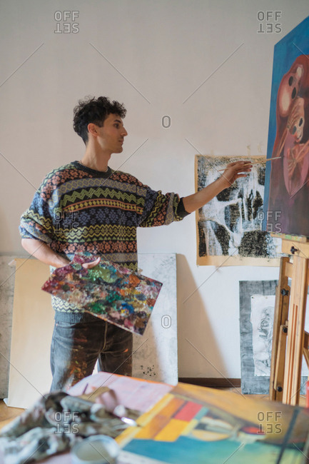 Male artist painting canvas in artists studio