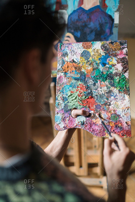 Over shoulder view of male artist mixing oil paint on palette in artists studio