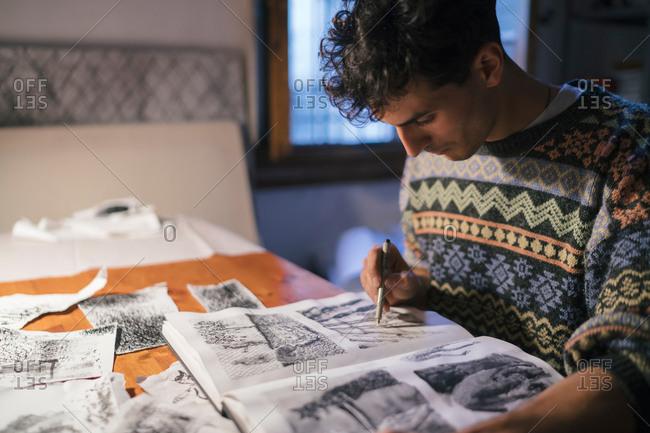 Male artist drawing in sketchbook at desk in artists studio