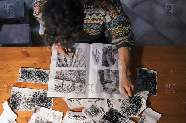Overhead view of male artist drawing in sketchbook in artists studio