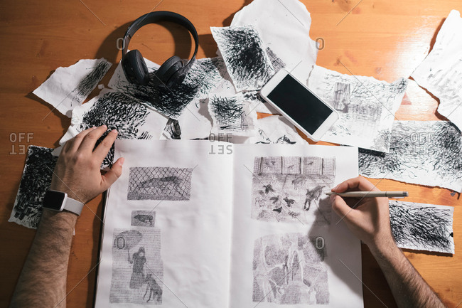 Overhead view of male artist drawing in sketchbook in artists studio, detail of hands