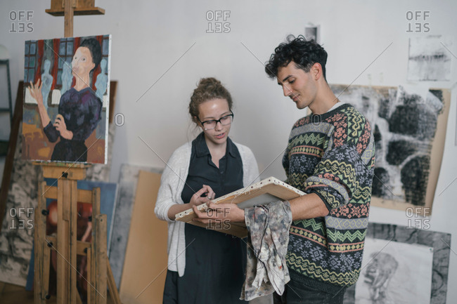 Male artist and female client looking at canvas in artists studio