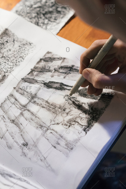 Male artist drawing in sketchbook in artists studio, over shoulder view